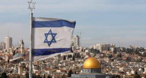 Izraeli zászló az Olajfák hegyén, a háttérben a jeruzsálemi óváros az al-Aksza-mecset kertjében álló Szikladóm (Omar-mecset) arany kupolájával 2017. december 5-én. Donald Trump amerikai elnök várhatóan december 6-án nyilatkozik arról, hogy az Egyesült Államok elismeri-e Jeruzsálemet Izrael fõvárosaként. (MTI/EPA/Abir Szultan)