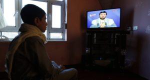 Szanaa, 2017. december 19. Abdel-Malik al-Húszi, a jemeni síita húszi lázadók parancsnoka televíziós beszédét nézi egy jemeni fiú a fővárosban, Szanaában 2017. december 19-én, miután a szaúdi vezetésű arab koalíció erői elfogták a lázadók egyik rakétáját, amelyet a rijádi királyi palotára irányítottak. (MTI/EPA/Jahja Arhab)