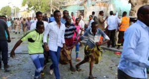 Sebesültet visznek szomáliai férfiak a fõváros, Mogadishu egyik belvárosi szállodája közelében, ahol autóba rejtett pokolgép robbant 2018. március 22-én. (MTI/EPA/Szaid Juszuf Varszame)